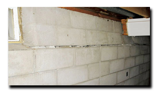 Bowed cement wall with horizontal crack  running along the cemen